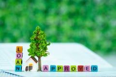 贷款文本和小模式房子和一点树与笔记本, s 免版税图库摄影