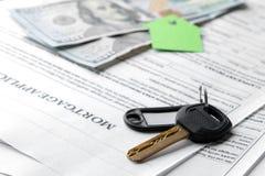 贷款申请 与房子钥匙表链的钥匙和空白和金钱在一张棕色木桌上 买家的概念 图库摄影