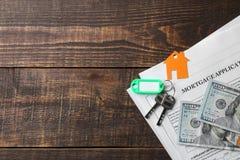 贷款申请 与房子钥匙表链的钥匙和空白和金钱在一张棕色木桌上 买家的概念 r 库存图片