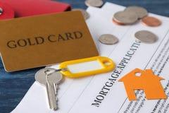 贷款申请 与房子keychain的钥匙和空白和金钱在一张蓝色木桌上 买家的概念 免版税库存图片