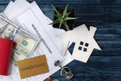 贷款申请 与房子keychain的钥匙和空白和金钱在一张蓝色木桌上 买家的概念 r 库存照片