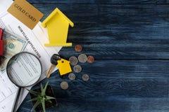 贷款申请 与房子keychain的钥匙和空白和金钱在一张蓝色木桌上 买家的概念 r 免版税图库摄影