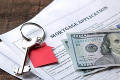 贷款申请 与红色keychain房子的钥匙和空白和金钱在一张棕色木桌上 买家的概念 免版税库存图片