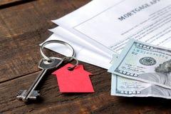 贷款申请 与红色keychain房子的钥匙和空白和金钱在一张棕色木桌上 买家的概念 免版税图库摄影