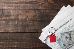 贷款申请 与红色keychain房子的钥匙和空白和金钱在一张棕色木桌上 买家的概念 r 免版税库存图片