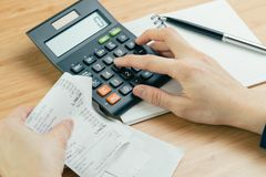 费用和费用演算或者票据付款概念,手在计算器上把手指和黑笔放在纸笔记薄 库存照片