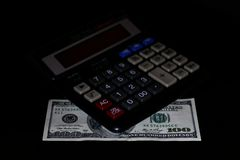 费用花费了,预算和税或者投资演算,与计算器的一百美元在深黑色背景桌上 免版税图库摄影