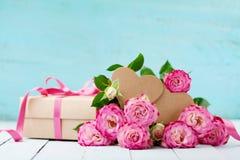 贺卡为生日、妇女或者母亲节 桃红色玫瑰开花和有丝带的礼物盒在绿松石桌上 淡色 图库摄影