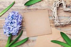 贺卡在与卡拉服特信封的母亲节装饰了风信花花和心脏在土气背景 顶视图 免版税库存图片