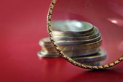 资本增加,在一小硬币stac前面的放大镜 库存图片