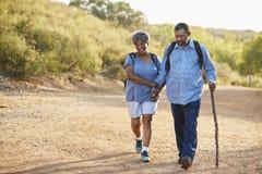 资深一起远足在乡下的夫妇佩带的背包 免版税库存图片