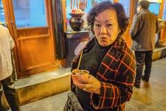 资深亚洲妇女肉丸画象照片在王府井走的街道和街道食物的在北京市, 库存图片