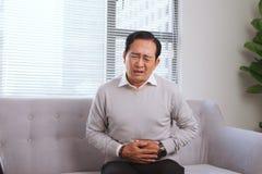 资深亚裔人以肚子疼,当坐沙发时 图库摄影