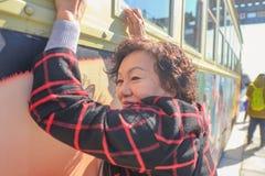 资深亚裔妇女画象照片有汽车的在qianmen街道 免版税图库摄影