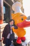 资深亚裔妇女画象照片有黄色鸭子的在北京市瓷的资本 免版税库存图片