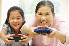 资深亚裔打电子游戏的妇女和女孩 免版税库存图片