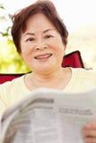 读资深亚裔的妇女户外 图库摄影