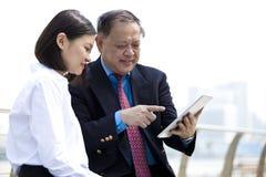 资深亚洲商人和使用片剂个人计算机的年轻女性亚裔执行委员 图库摄影