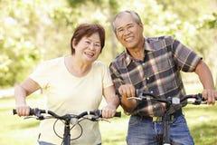 资深亚洲夫妇骑马自行车在公园 库存照片