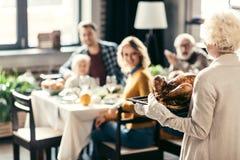 资深假日晚餐的妇女运载的感恩火鸡 免版税库存图片