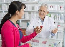 资深化学家和妇女有处方的在药房 免版税库存图片