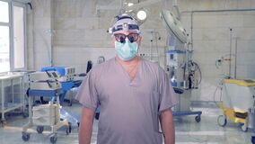 资深医生画象有站立在手术的照相机前面的现代医疗设备的 股票视频