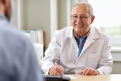 资深医生谈话与男性患者在医院 免版税库存照片
