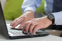资深商人为工作使用膝上型计算机 免版税库存照片