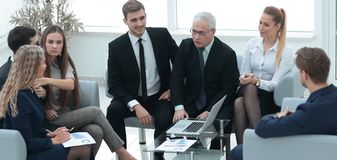 资深商人和事务合作坐在现代办公室的大厅 免版税库存图片