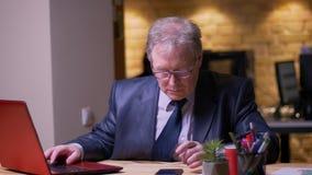 资深商人画象在正式服装的同时与膝上型计算机和智能手机一起使用在办公室 股票视频