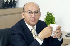 资深商人饮用的咖啡,当坐在他的工作地点时 免版税库存图片