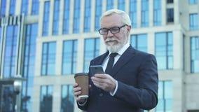 资深在午餐时间,在智能手机的卷动期间的商人饮用的咖啡 股票视频