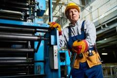 资深在工厂的工作者运行的机器 库存照片
