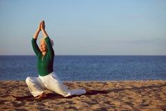 资深在海滩的女子实践的瑜伽 图库摄影