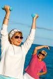 资深在海滩的妇女举的重量。 免版税库存图片