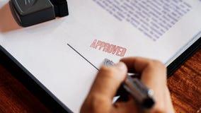 资深在证明合同的商人男性手投入的或签署的署名以后批准在贷款文件的邮票 库存照片