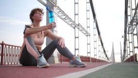 资深在锻炼以后的红头发人妇女饮用水 股票视频