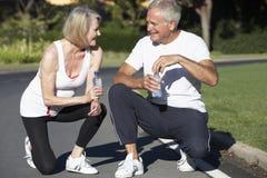 资深在锻炼以后的夫妇休息的和饮用水 免版税库存图片
