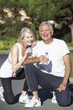资深在锻炼以后的夫妇休息的和饮用水 库存照片