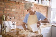 资深夫人在厨房里 免版税库存图片