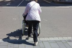 资深夫人轮椅协助 免版税库存照片