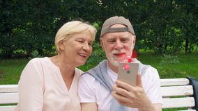资深夫妇变冷静与桃红色便携式的通风设备附加手机在热期间在公园 股票视频