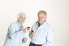 资深夫妇听到音乐 库存图片