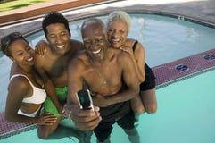 资深夫妇和中间成人结合摆在手机照片的在游泳池被举起的视图。 免版税库存图片