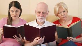 资深夫妇和青少年的女儿读书打印书 传统古典纸读书的概念 股票视频