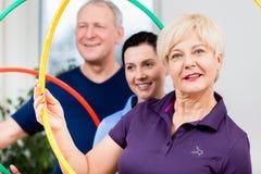 资深夫妇在做与hula箍的物理疗法方面锻炼 免版税库存照片