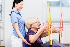 资深夫妇在做与hula箍的物理疗法方面锻炼 图库摄影