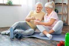 资深夫妇在家一起行使医疗保健健康营养 免版税库存照片