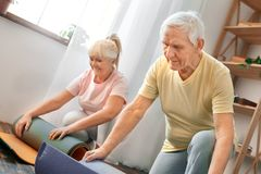 资深夫妇在家一起行使医疗保健辗压瑜伽席子认为 库存图片