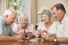 资深夫妇在家享受卡片的比赛小组 库存照片